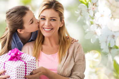 happy mother and daughter offering gift