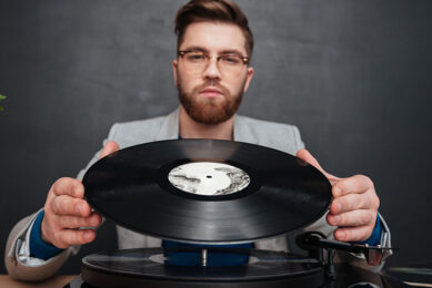 man using turntable and vinyl record