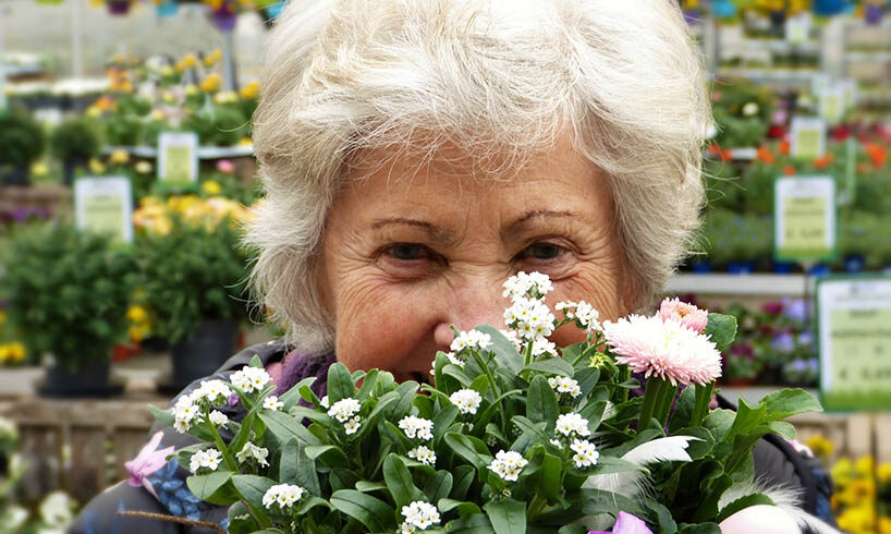 senior woman behind a handful of flowers
