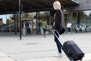 young woman traveling with a wheeled suitcase